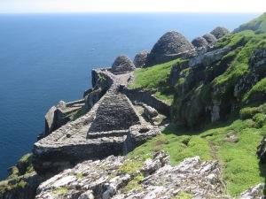 A flanc de falaise, les ruines du monastère et les bories aux toits arrondis. Photo visible sur le site skelligislands.com