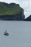 Le bateau nous attend, minuscule sur l'océan. Au fond, l'île de Dùn ©Camille Peney
